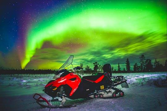 Viagem de fotografia de mota de neve com a aurora
